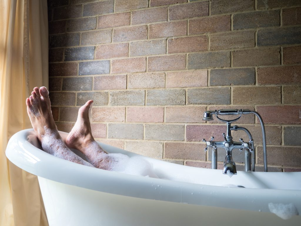Man's feet handing out of his bubble bath